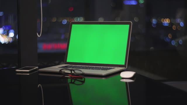 vidéos et rushes de dolly a tiré de l'ordinateur portatif avec l'écran vert la nuit, aucun peuple - bureau pièce