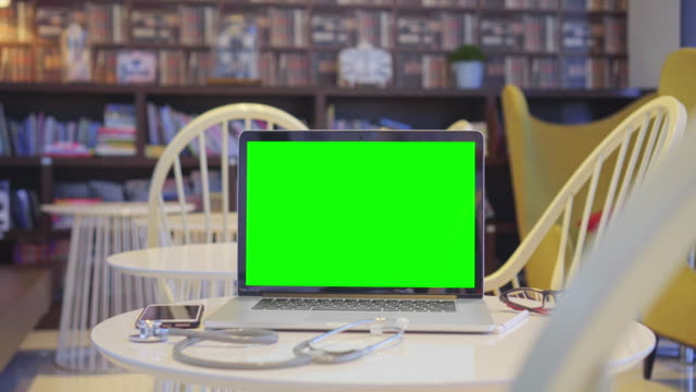 dolly shot of computer laptop with green screen in a library,no people - laptops in a row stock videos & royalty-free footage