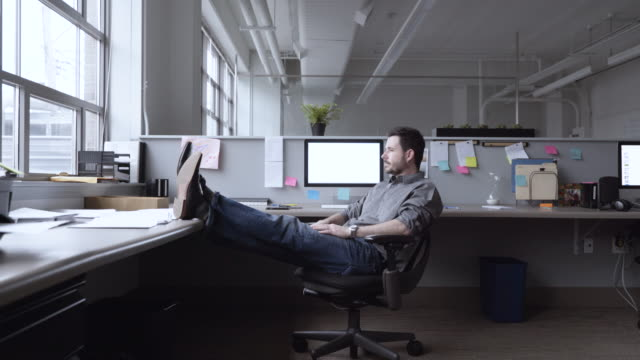 Dolly shot of confident businessman relaxing while sitting on chair in office