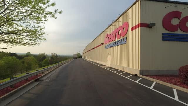 dolly shot of costco wholesale store signature sunset amid the global coronavirus pandemic in georgia, atlanta on april 7, 2021. - catena di negozi video stock e b–roll