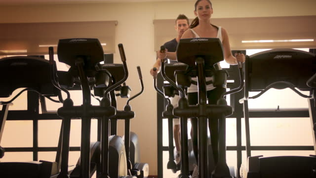 dolly shot of couple at gym exercising on cross trainer. - cross trainer stock videos & royalty-free footage
