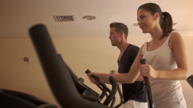 dolly shot of couple at gym exercising on cross trainer. - cross trainer stock videos and b-roll footage