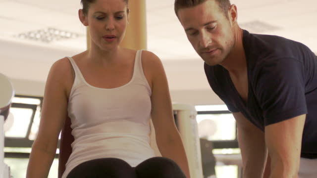 Dolly shot of couple exercising at gym.