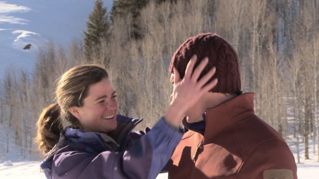 dolly shot of couple hugging and kissing outdoors in the snow / ketchum, idaho, united states - スキーウェア点の映像素材/bロール