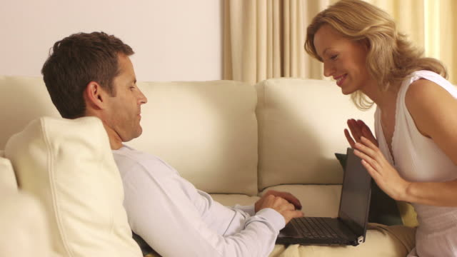 dolly shot of couple on couch together/marbella region, spain - tre quarti video stock e b–roll