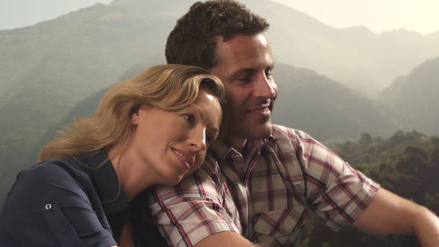 Dolly shot of couple sitting together on mountain peak/Marbella region, Spain