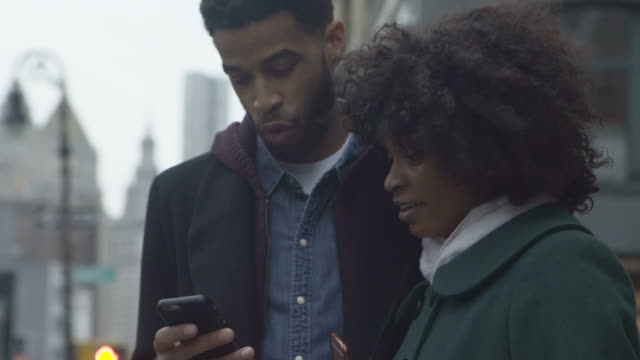 Dolly shot of couple using smart phone while standing in city