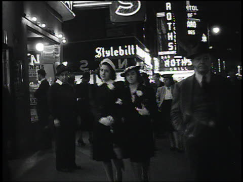 1940 B/W dolly shot of crowded sidewalk in Times Square at night / New York City