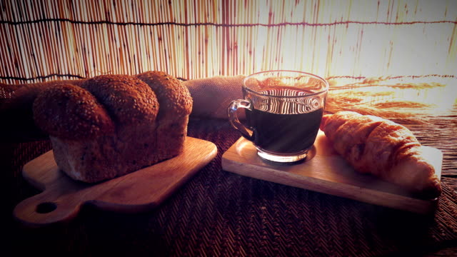 Dolly shot of Cup of coffee with bread.