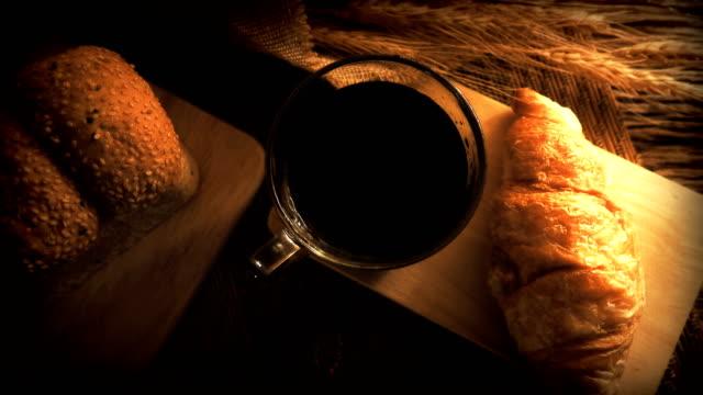 クロワッサンとコーヒーのカップのドリー ショット。 - カフェイン分子点の映像素材/bロール