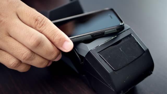 vídeos y material grabado en eventos de stock de dolly shot del cliente haciendo el pago sin contacto con el teléfono inteligente. - pago por móvil