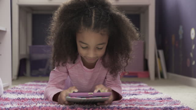 dolly shot of cute girl using tablet computer while lying on rug at home - frizzy hair stock videos and b-roll footage