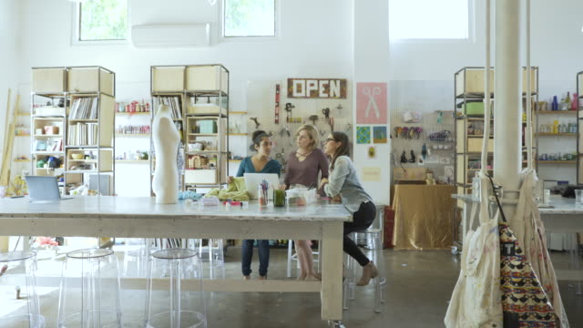 Dolly shot of design professionals discussing at desk in creative office