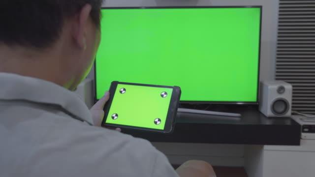 vidéos et rushes de travelling sur chariot de tablette numérique et télévision écran vert - stylo