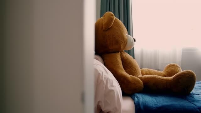 dolly shot of empty bedroom with teddy bear sitting on it. warm look. - teddy bear stock videos & royalty-free footage