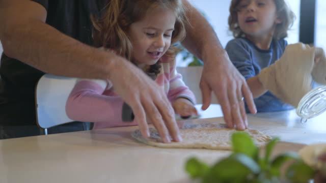 vídeos de stock e filmes b-roll de dolly shot of father assisting children in making dough at kitchen - genderblend