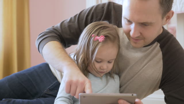 stockvideo's en b-roll-footage met dolly shot of father assisting daughter in using tablet computer at home - genderblend