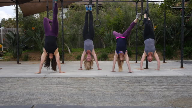 Dolly shot of female athletes doing handstands at outdoor gym