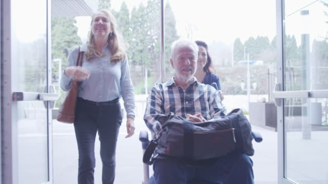 dolly shot of female doctor with coworker pushing patient sitting in wheelchair while entering in hospital - entrance stock videos & royalty-free footage