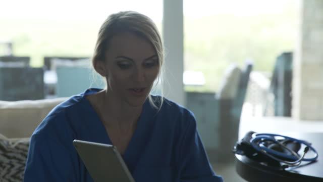vidéos et rushes de dolly shot of female home caregiver showing tablet computer to senior woman in living room - équipement