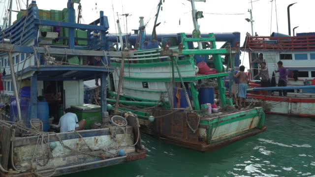 dolly shot of fishermen tying boats with ropes at harbor against sky - 固定された点の映像素材/bロール
