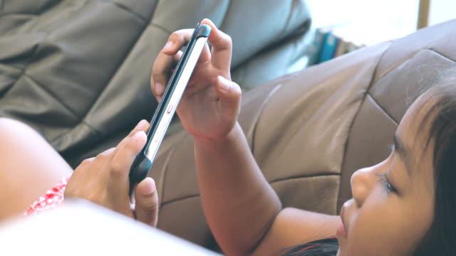 Dolly schot van meisje geniet van het spelen van de smartphone.