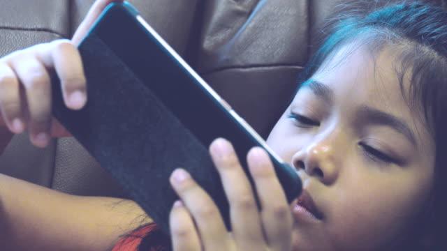 dolly-schuss von mädchen genießen das smartphone spielen. - sportschützer stock-videos und b-roll-filmmaterial