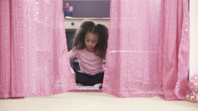dolly shot of girl reading book while sitting on floor amidst pink curtains at home - sitting on floor stock videos and b-roll footage