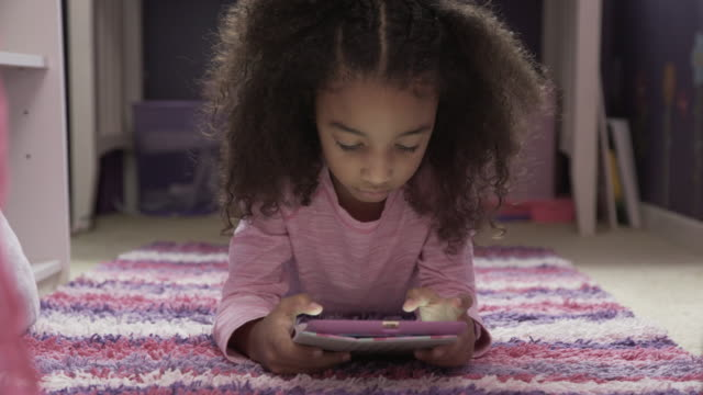 dolly shot of girl using tablet computer while lying on rug at home - frizzy hair stock videos and b-roll footage