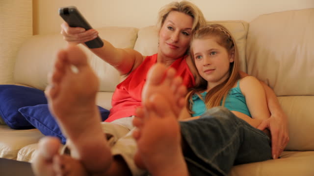 dolly shot of grandmother and granddaughter watching tv together indoors. - barefoot stock videos & royalty-free footage