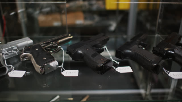 dolly shot of guns in retail display case - arma da fuoco video stock e b–roll