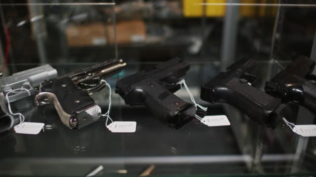dolly shot of guns in retail display case - gun stock videos & royalty-free footage