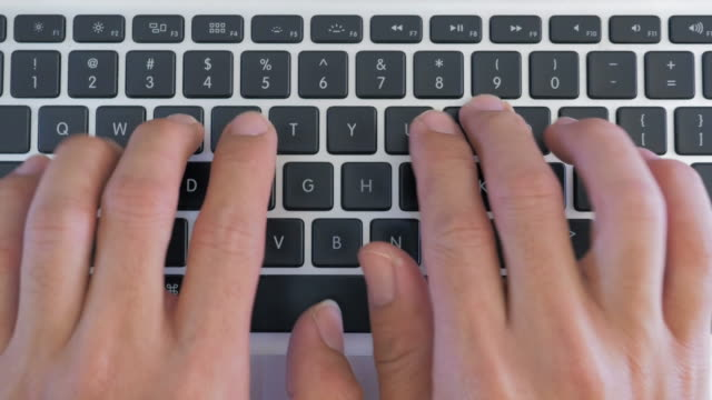 Dolly shot of Hand typing on a laptop keyboard