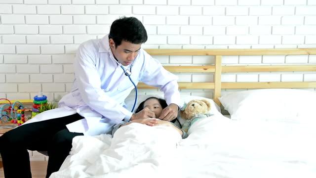 不眠症睡眠の問題について若い女の子の患者をチェック聴診を使用してハンサムな男性医師のドリーショット - 無呼吸点の映像素材/bロール
