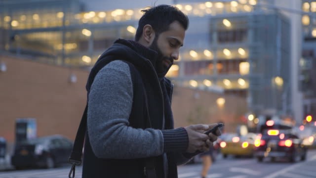 dolly shot of handsome man using mobile phone while standing on city street at dusk - one mid adult man only stock videos & royalty-free footage