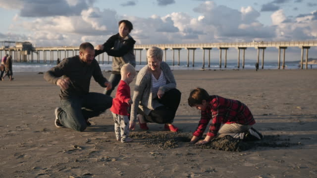 stockvideo's en b-roll-footage met dolly shot of happy family at beach against cloudy sky - familie met drie kinderen