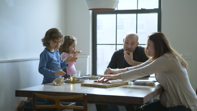 dolly shot of happy family eating pizza at dining table - unhealthy eating点の映像素材/bロール