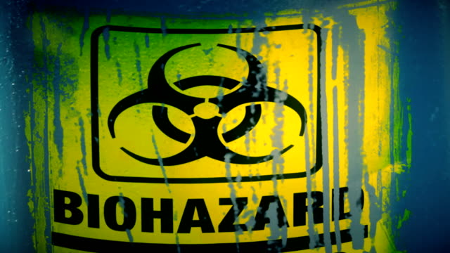 dolly shot of hazardous waste container with warning label for biohazard in english and spanish peligroso - hazardous area sign stock videos & royalty-free footage