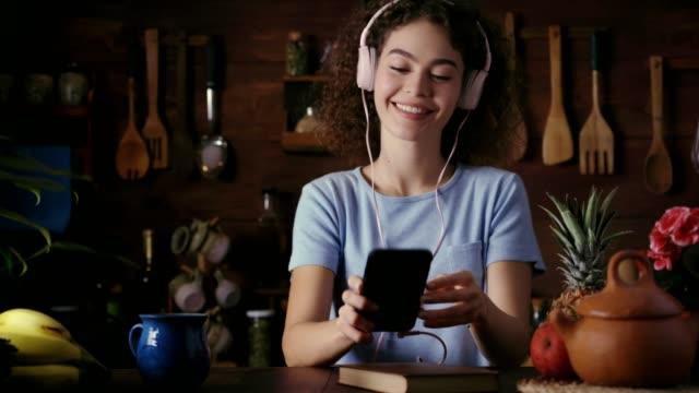 vídeos de stock, filmes e b-roll de dolly tiro de cabelo encaracolado hispânico adolescente ouvindo música no telefone inteligente na cozinha rústica - sacudindo