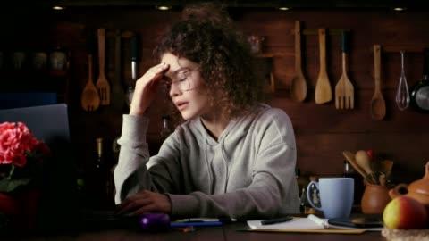 vídeos de stock, filmes e b-roll de dolly disparou da mulher nova tired do cabelo curly latino-americano que usa o portátil no escritório home - frustração