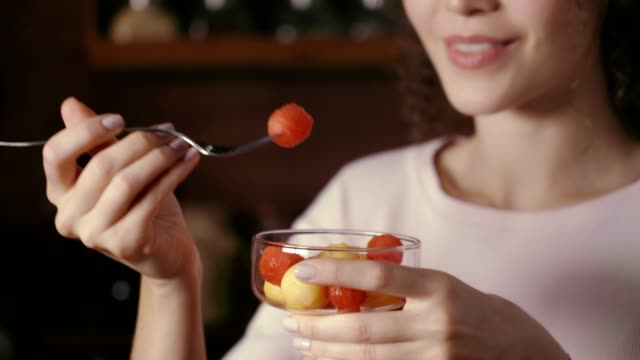 dolly shot of hispanic curly hair young woman eating fruit salad in a rustic kitchen - fruit salad stock videos & royalty-free footage
