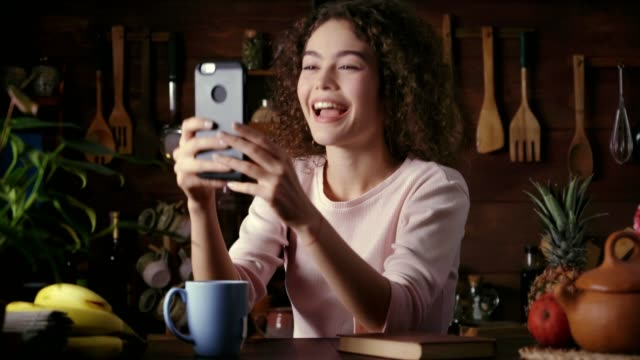 dolly shot of hispanic curly hair young woman making video call with a friend on a cellphone in a rustic kitchen - video call stock videos & royalty-free footage