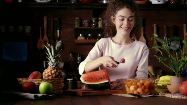 dolly shot of hispanic curly hair young woman preparing fruit salad in a rustic kitchen - fruit salad stock videos & royalty-free footage