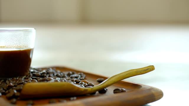 コーヒー豆で飾られた木製のトレイにカップに熱いコーヒーのドリー ショット - カフェイン分子点の映像素材/bロール