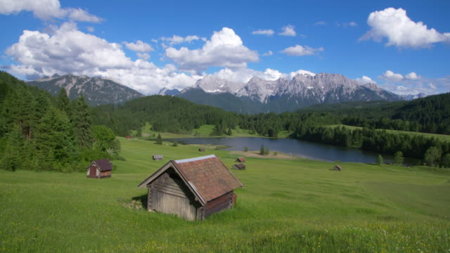 Dolly Shot of Lake Geroldsee with huts and Karwendel mountains in background. Geroldsee, Mittenwald, Garmisch-Partenkirchen, Bavarian Alps, Karwendel mountains, Bavaria, Germany.