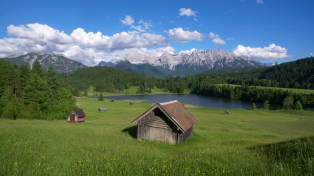 dolly shot of lake geroldsee with huts and karwendel mountains in background. geroldsee, mittenwald, garmisch-partenkirchen, bavarian alps, karwendel mountains, bavaria, germany. - hut stock videos & royalty-free footage