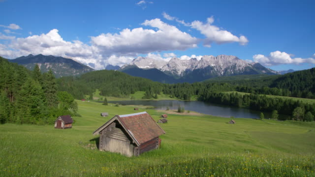 dolly shot of lake geroldsee with huts and karwendel mountains in background. geroldsee, mittenwald, garmisch-partenkirchen, bavarian alps, karwendel mountains, bavaria, germany. - bavarian alps stock videos & royalty-free footage