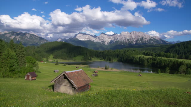 dolly shot of lake geroldsee with huts and karwendel mountains in background. geroldsee, mittenwald, garmisch-partenkirchen, bavarian alps, karwendel mountains, bavaria, germany. - 小屋点の映像素材/bロール