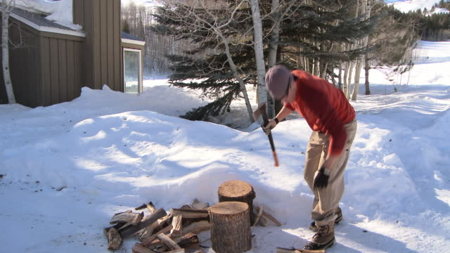 Dolly shot of man chopping wood in the snow / Ketchum, Idaho, United States