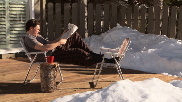 dolly shot of man drinking coffee and reading the newspaper on front deck of home / ketchum, idaho, united states - piedi alzati video stock e b–roll